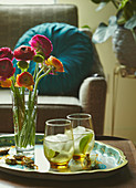 Two drinks and a vase with flowers on a tray in a living room