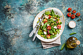 Salad with arugula, cherry tomatoes, cream cheese, pesto sauce and herbs
