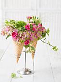 Gestecke mit Rosen und Hortensien in Eistüten
