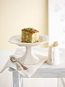 Limetten-Mohnkuchen, ein Stück auf Kuchenständer