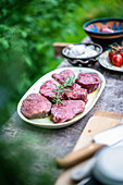 Raw beef loin steaks with ingredients in a garden kitchen