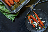 Roasted carrots with feta cheese on a black plate and in a roasting pan, on a black background