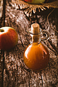 Bottle of apple organic vinegar on wooden background