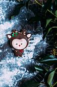Lebkuchenplätzchen (Tierfigur) mit grünen Blättern zu Weihnachten