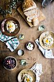 Spiegelei und Feta auf Pitabrot, Sauerteigbrot, Trauben und Wassergläser
