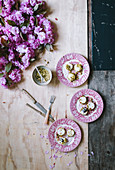 Pistachio goatcheese with rose petals on French plates with pink blossom on a wooden background