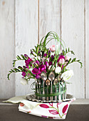 A centrepiece featuring freesias and buttercups decorated with vintage spoons