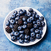 Blueberry and blackberry berries on a white plate on blue stone background