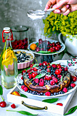 Summer fruit tart with berries, apricots, cherries and icing sugar