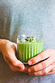 Green vegan smoothie with spinach, banana and sprouted seeds in glass in male hands