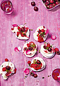 Mini pavlovas with cherries, raspberries and pistachios