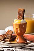 Weich gekochtes Frühstücksei im Eierbecher mit knuprigen Toaststicks