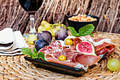Italian antipasti plate with ham, salami, cheeses, olives, figs and wine