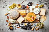 Various types of cheese on wooden cutting board