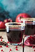 Granatapfelsaft und frische Granatäpfel
