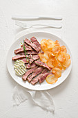 Sliced loin steak with lemon and herb butter and potato crisps