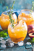 Peach cocktail or tea with ice and thyme
