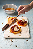 Polenta fritters with red pesto, brie and rosemary honey