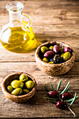 Wooden table with olives and olive oil