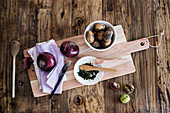 Potatoes, herbs and red onions on a wooden board