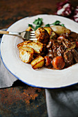Beef bourguignon in ceramic plate with baked potatoes on metallic background