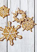 Winterliche Sternenplätzchen mit Band an Holzwand hängend