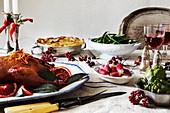 Festlich gedeckter Tisch mit Entenbraten, Beilagen und Wein