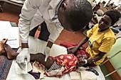 Doctor examining a leg wound