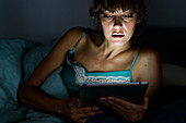 Woman using a digital tablet at night