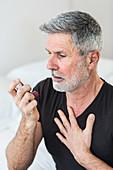 Man using an inhaler during an asthma attack