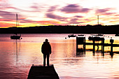 A man watches the sunset at Waterhead, UK