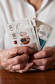 Close-up of elderly woman holding British banknotes