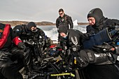 SCUBA divers returning to boat after diving next to iceberg