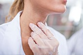 Doctor feeling her larynx