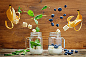 Spinach banana and blueberry banana smoothie with flying slices on a wood background