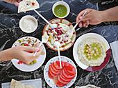 Menschen essen zusammen gemischte arabische Vorspeisen mit Fladenbrot