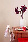 Deep red amaryllis in white vase on wooden table