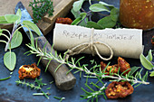 A roll of paper with a recipe collection, rosemary and dried tomatoes