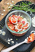 Tomato salad with onion rings and bean sprouts in a jar