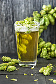 A glass of light beer with hops