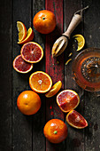 Blood oranges cut, halved, sliced and juiced with wooden juicing tool on rustic dark wooden background with red stripe