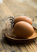 Two fresh eggs in a wooden dish and a spotty feather on a rustic wooden table