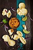 Mini popadoms with dal dip limes and red onion