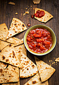 Small bowl and tomato salsa served with handmade tortilla chips on a rustic wooden board