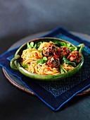 Meatballs with noodles, vegetables, and sesame seeds