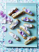 Violet eclairs, with icing and petals