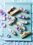 Veilchen-Eclairs mit Zuckerglasur und Blütenblättern