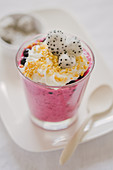 Pudding with wild berries, whipped cream, nuts and dragon fruit