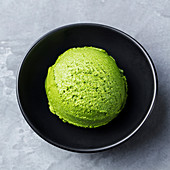 Green tea matcha ice cream scoop in black bowl on a grey stone background