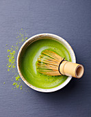 Matcha green tea cooking process in a bowl with bamboo whisk. Black slate background